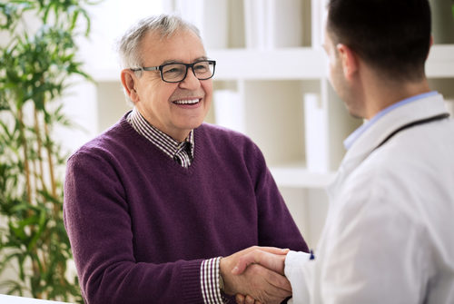Smiling happy healthy old male shaking with doctor
